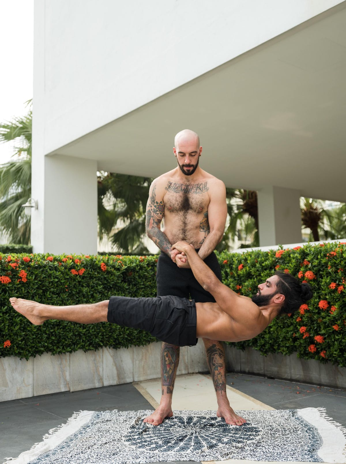 Shirtless strong sportsmen practicing acro yoga 4334988
