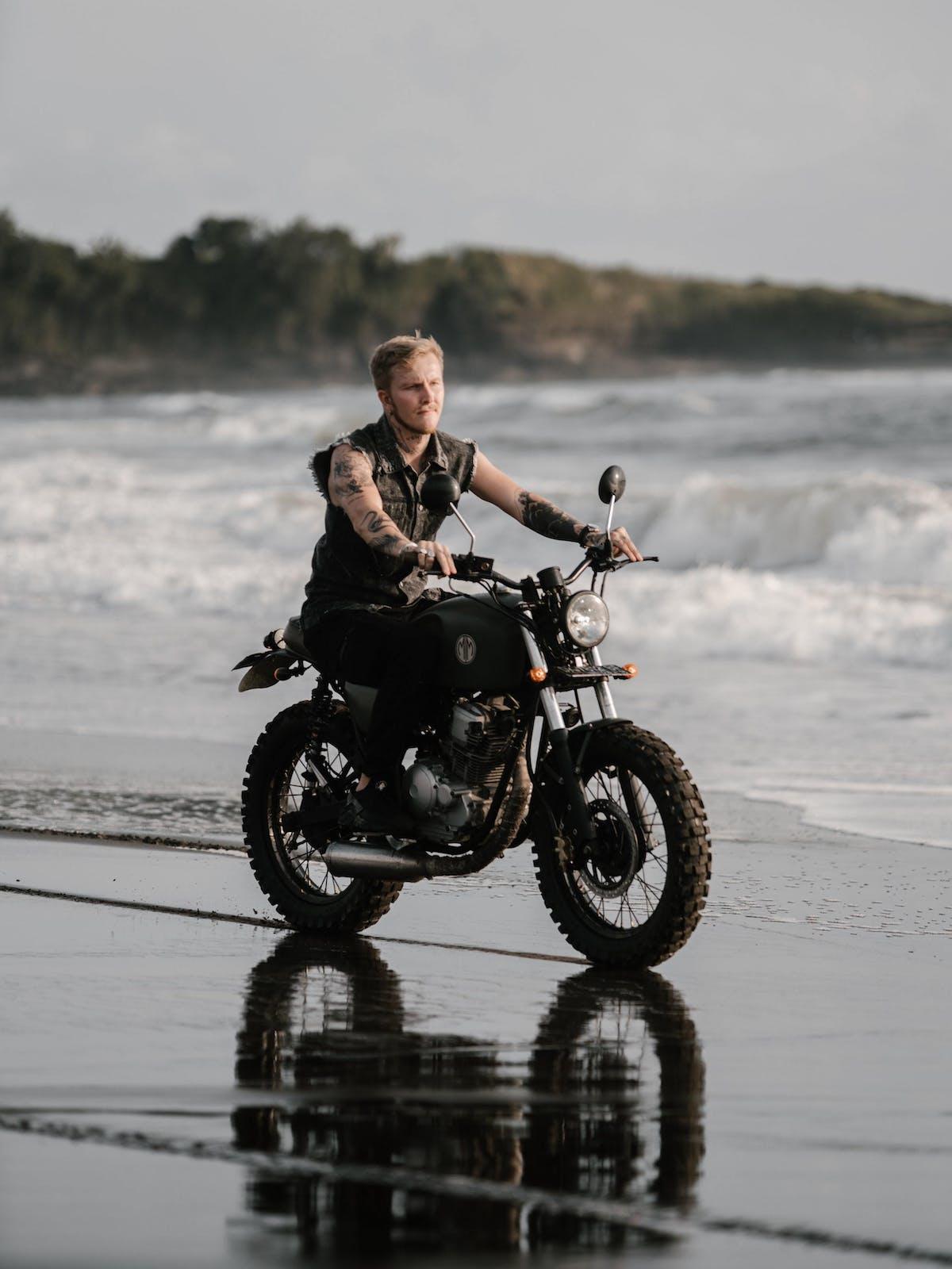 Tattooed motorcyclist riding bike along ocean coast in 4348221