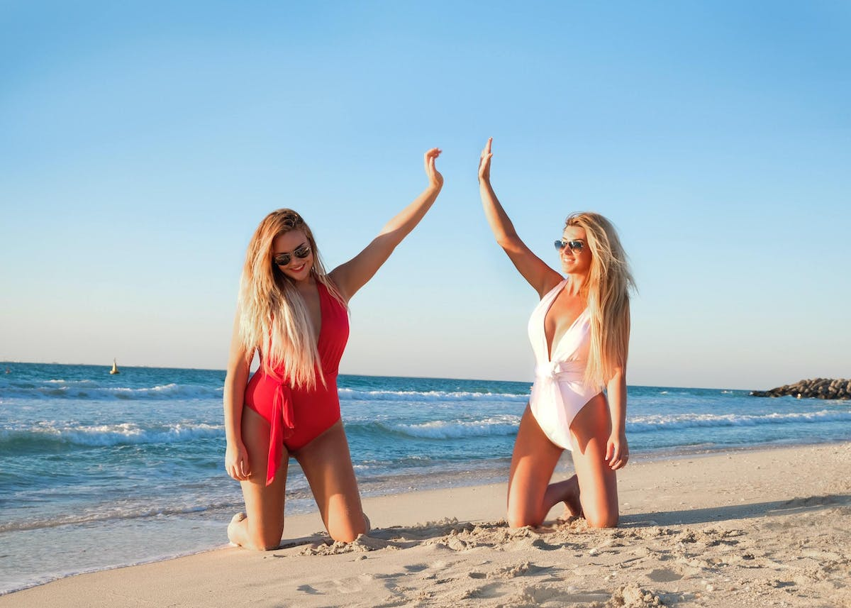 Two woman kneeling on white sand beach 1089628
