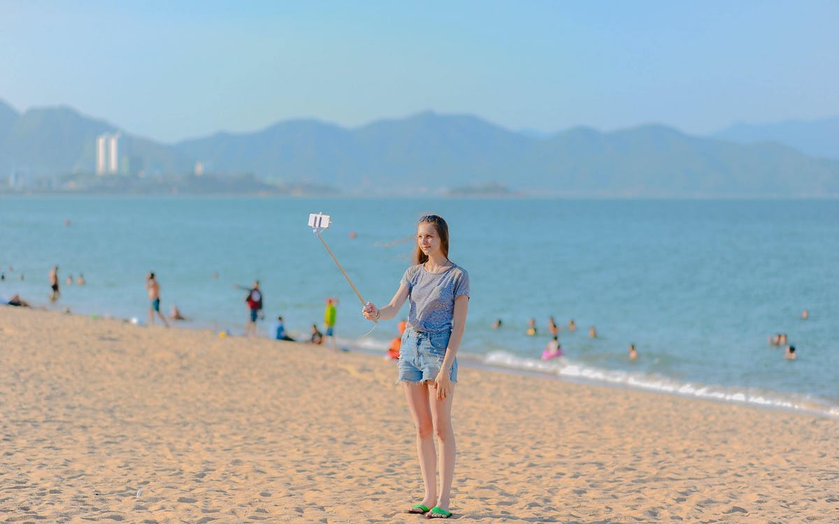 Woman standing on seashore taking selfie using monopod at 1213974